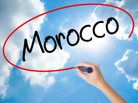 fes: Woman Hand Writing Morocco  with black marker on visual screen. Isolated on Sunny Sky. Business concept. Stock Photo