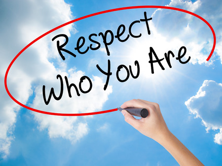 Woman Hand Writing Respect Who You Are with black marker on visual screen. Isolated on Sunny Sky. Business concept. Stock Photo Stock Photo