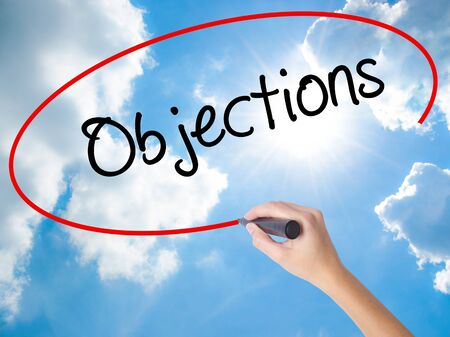 objections: Woman Hand Writing Objections  with black marker on visual screen. Isolated on Sunny Sky. Business concept. Stock Photo