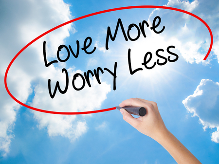 Woman Hand Writing Love More Worry Less with black marker on visual screen. Isolated on Sunny Sky. Business concept. Stock Photo