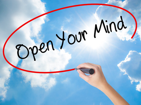 Woman Hand Writing Open Your Mind with black marker on visual screen. Isolated on Sunny Sky. Business concept. Stock Photo Stock Photo