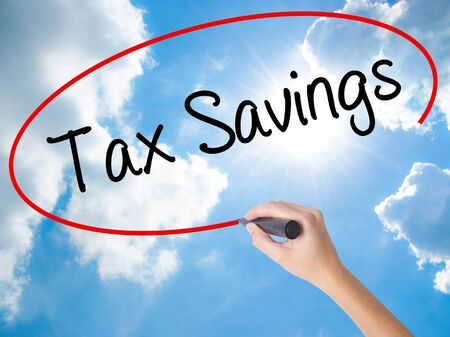 Woman Hand Writing Tax Savings with black marker on visual screen. Isolated on Sunny Sky. Business concept. Stock Photo Stock Photo