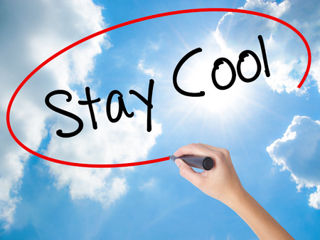Woman Hand Writing Stay Cool   with black marker on visual screen. Isolated on Sunny Sky. Business concept. Stock Photo