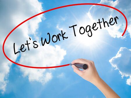 combined effort: Woman Hand Writing Lets Work Together with black marker on visual screen. Isolated on Sunny Sky. Business concept. Stock Photo