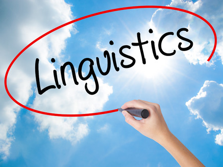 Woman Hand Writing Linguistics  with black marker on visual screen. Isolated on Sunny Sky. Business,  technology, internet concept. Stock Photo