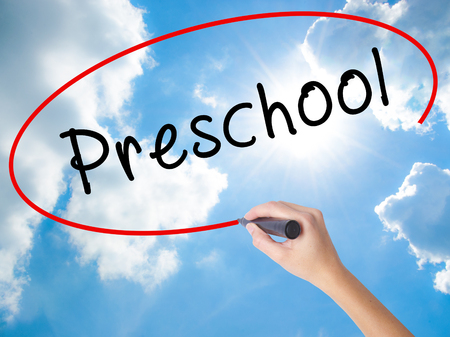 Woman Hand Writing Preschool with black marker on visual screen. Isolated on Sunny Sky. Business concept. Stock Photo
