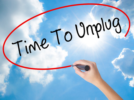 unplugging: Woman Hand Writing Time To Unplug with black marker on visual screen. Isolated on Sunny Sky. Business concept. Stock Photo
