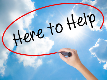 Woman Hand Writing Here to Help with black marker on visual screen. Isolated on Sunny Sky. Business concept. Stock Photo