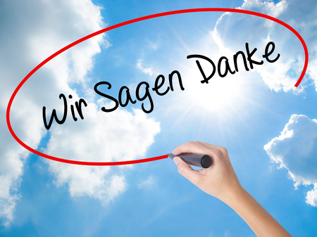Woman Hand Writing Wir Sagen Danke (We Say Thank You In German)   with black marker on visual screen. Isolated on Sunny Sky. Business concept. Stock Photo