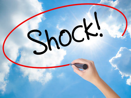 Woman Hand Writing Shock! with black marker on visual screen. Isolated on Sunny Sky. Business concept. Stock Photo Stock Photo