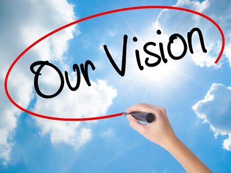 Woman Hand Writing Our Vision with black marker on visual screen. Isolated on Sunny Sky. Business concept. Stock Photo