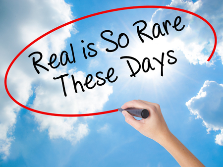 Woman Hand Writing Real is So Rare These Days with black marker on visual screen. Isolated on Sunny Sky. Business concept. Stock Photo
