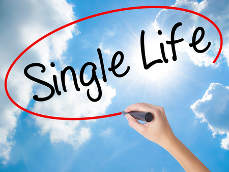 Woman Hand Writing Single Life with black marker on visual screen. Isolated on Sunny Sky. Business concept. Stock Photo Stock Photo