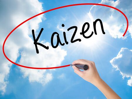 Woman Hand Writing Kaizen with black marker on visual screen. Isolated on Sunny Sky. Business concept. Stock Photo Stock Photo