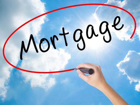 Woman Hand Writing Mortgage with black marker on visual screen. Isolated on Sunny Sky. Business concept. Stock Photo