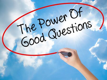 Woman Hand Writing The Power Of Good Questions with black marker on visual screen. Isolated on Sunny Sky. Business concept. Stock Photo