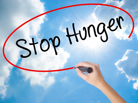 malnutrition: Woman Hand Writing  Stop Hunger with black marker on visual screen. Isolated on Sunny Sky. Business concept. Stock Photo