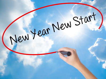 Woman Hand Writing New Year New Start with black marker on visual screen. Isolated on Sunny Sky. Business concept. Stock Photo