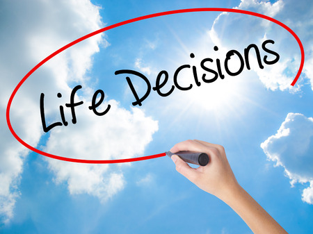 Woman Hand Writing Life Decisions with black marker on visual screen. Isolated on Sunny Sky. Business concept. Stock Photo
