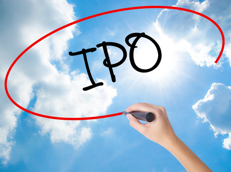 Woman Hand Writing IPO (Initial Public Offering)   with black marker on visual screen. Isolated on Sunny Sky. Business concept. Stock Photo Archivio Fotografico