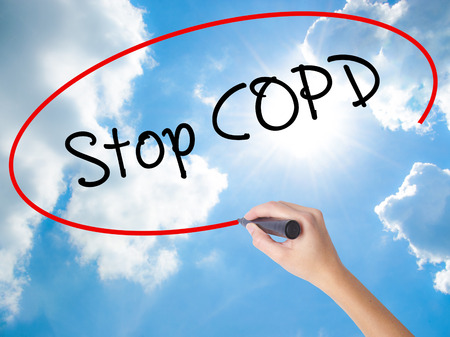 tosiendo: Woman Hand Writing Stop COPD with black marker on visual screen. Isolated on Sunny Sky. Business concept. Stock Photo Foto de archivo