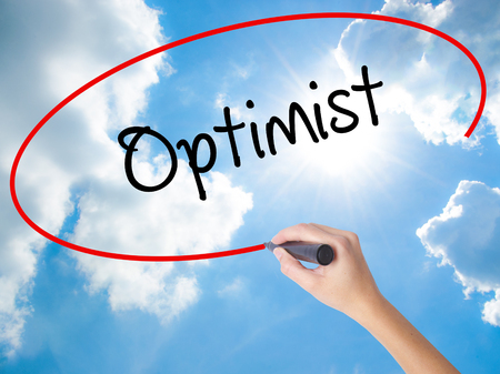 Woman Hand Writing Optimist  with black marker on visual screen. Isolated on Sunny Sky. Business concept. Stock Photo Stock Photo