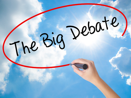 Woman Hand Writing The Big Debate with black marker on visual screen. Isolated on Sunny Sky. Business concept. Stock Photo