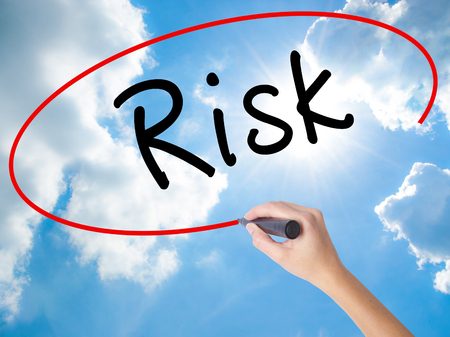 reduce risk: Woman Hand Writing Risk with black marker on visual screen. Isolated on Sunny Sky. Business concept. Stock Photo Stock Photo