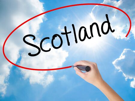 Woman Hand Writing Scotland with black marker on visual screen. Isolated on Sunny Sky. Business, technology, internet concept. Stock  Photo