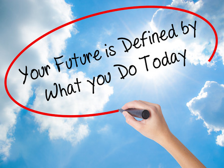 Woman Hand Writing Your Future is Defined by What you Do Today  with black marker on visual screen. Isolated on Sunny Sky. Business concept. Stock Photo Stock Photo