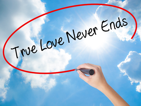 waits: Woman Hand Writing True Love Never Ends with black marker on visual screen. Isolated on Sunny Sky. Business concept. Stock Photo Stock Photo