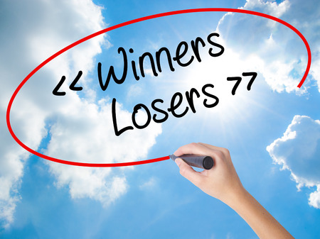 Woman Hand Writing Winners - Losers  with black marker on visual screen. Isolated on Sunny Sky. Business concept. Stock Photo