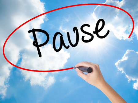 Woman Hand Writing Pause with black marker on visual screen. Isolated on Sunny Sky. Business concept. Stock Photo