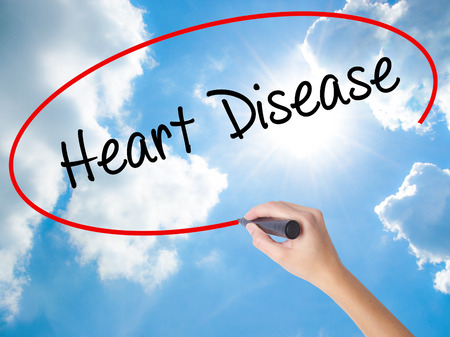 Woman Hand Writing Heart Disease with black marker on visual screen. Isolated on Sunny Sky. Business concept. Stock Photo Stock Photo