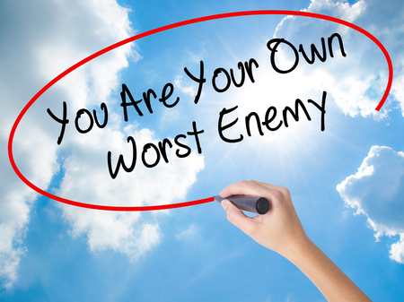 Woman Hand Writing You Are Your Own Worst Enemy with black marker on visual screen. Isolated on Sunny Sky. Business concept. Stock Photo