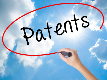 patents: Woman Hand Writing Patents with black marker on visual screen. Isolated on Sunny Sky. Business concept. Stock Photo Stock Photo