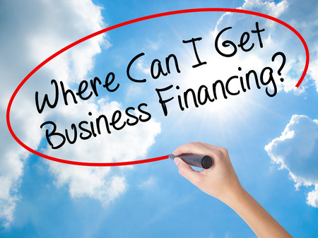 Woman Hand Writing Where Can I Get Business Financing? with black marker on visual screen. Isolated on Sunny Sky. Business concept. Stock Photo Stock Photo
