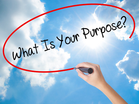 Woman Hand Writing What Is Your Purpose?  with black marker on visual screen. Isolated on Sunny Sky. Business concept. Stock Photo Stock Photo