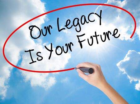 descendants: Woman Hand Writing Our Legacy Is Your Future  with black marker on visual screen. Isolated on Sunny Sky. Business concept. Stock Photo