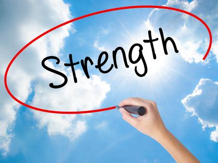 Woman Hand Writing Strength with black marker on visual screen. Isolated on Sunny Sky. Business concept. Stock Photo