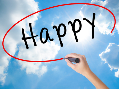 Woman Hand Writing Happy black marker on visual screen. Isolated on Sunny Sky. Business concept. Stock Photo