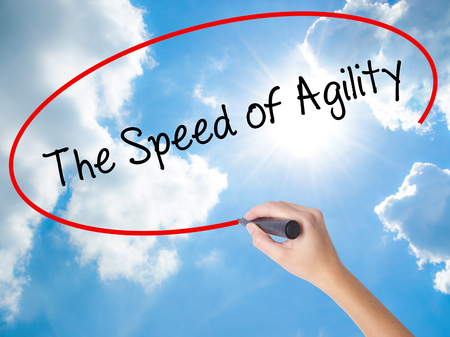 Woman Hand Writing The Speed of Agility with black marker on visual screen. Isolated on Sunny Sky. Business concept. Stock Photo Stock Photo