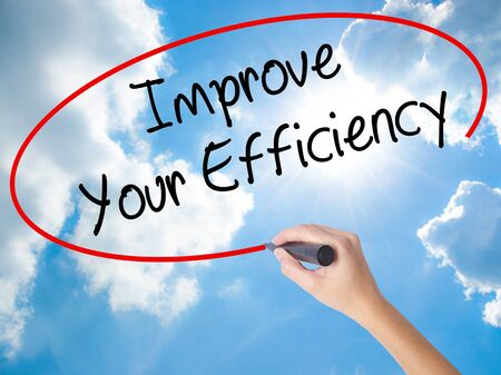 proficiency: Woman Hand Writing Improve Your Efficiency with black marker on visual screen. Isolated on Sunny Sky. Business concept. Stock Photo