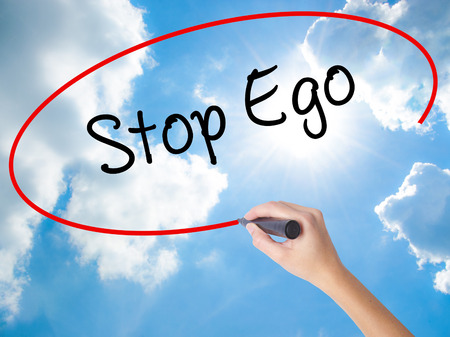 self care: Woman Hand Writing  Stop Ego with black marker on visual screen. Isolated on Sunny Sky. Business concept. Stock Photo