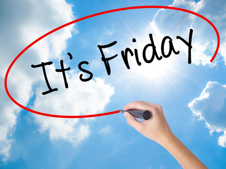 Woman Hand Writing Its Friday with black marker on visual screen. Isolated on Sunny Sky. Business concept. Stock Photo