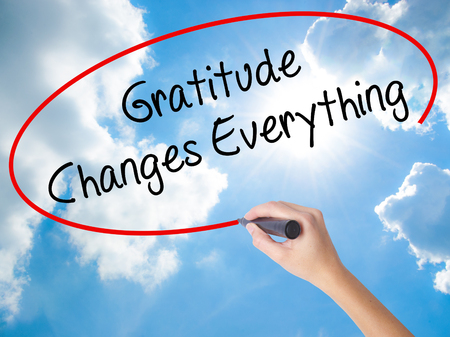 Woman Hand Writing Gratitude Changes Everything with black marker on visual screen. Isolated on Sunny Sky. Business concept. Stock Photo Stock Photo