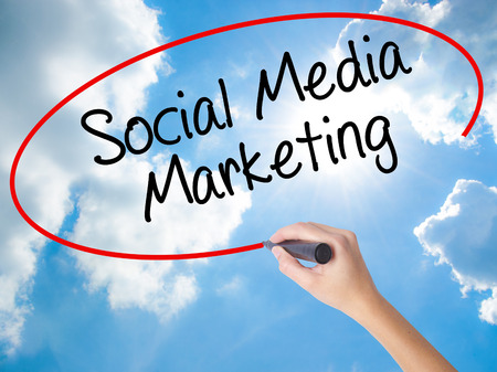 Woman Hand Writing Social Media Marketing with black marker on visual screen. Isolated on Sunny Sky. Business concept. Stock Photo