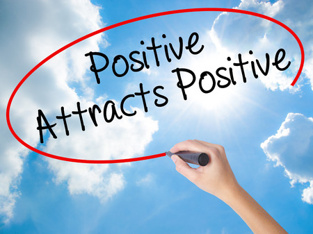 positiveness: Woman Hand Writing Positive Attracts Positive with black marker on visual screen. Isolated on Sunny Sky. Business concept. Stock Photo