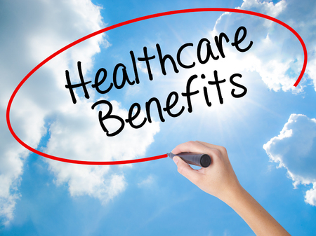 Woman Hand Writing Healthcare Benefits with black marker on visual screen. Isolated on Sunny Sky. Business concept. Stock Photo