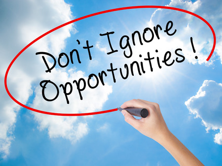 Woman Hand Writing Dont Ignore Opportunities black marker on visual screen. Isolated on Sunny Sky. Business concept. Stock Photo